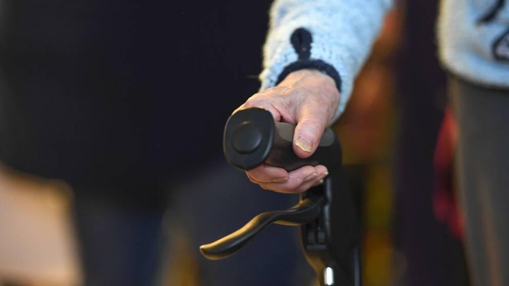 En äldre person tar sig runt med hjälp av en rollator på ett äldreboende.