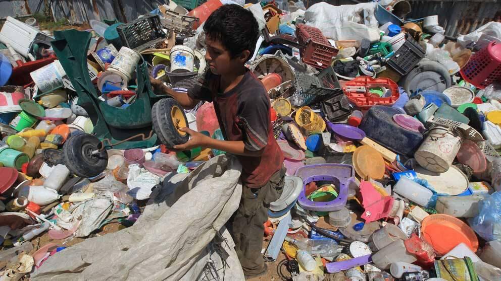 En pojke i Beit Lahia, norra Gaza, samlar plast och metall som han hoppas kunna sälja.