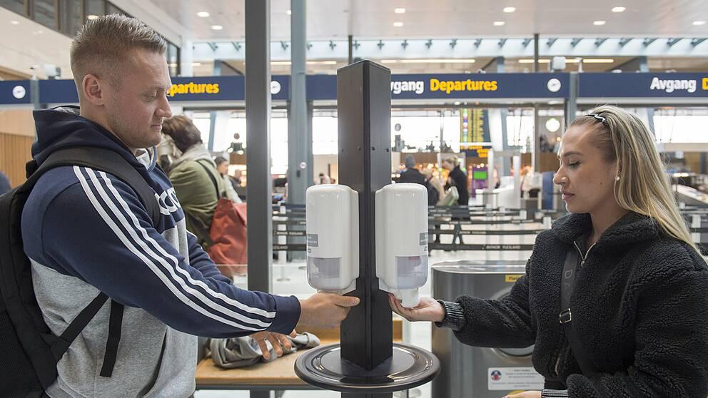 Två resenärer tvättar händerna på flygplatsen i Bergen.