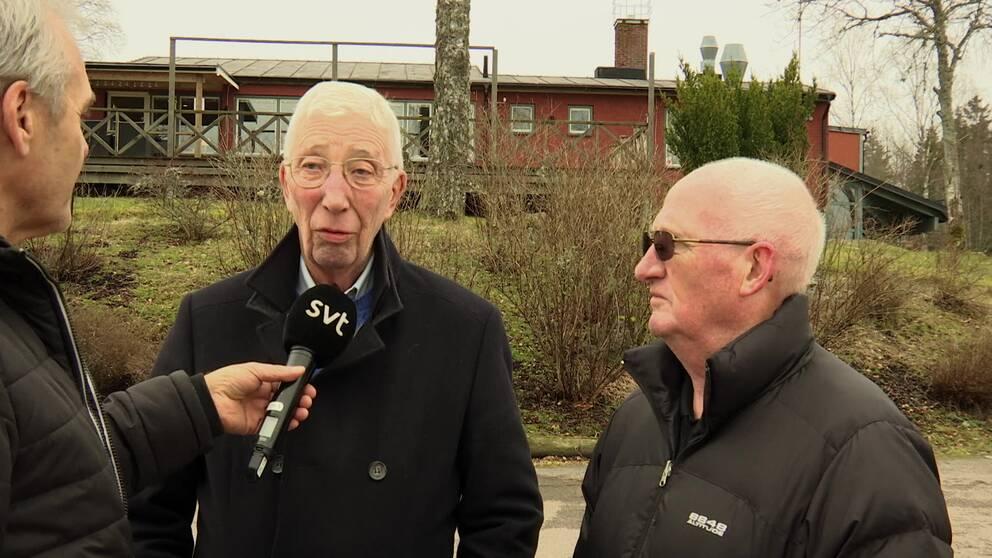 Två äldre män blir intervjuade utomhus