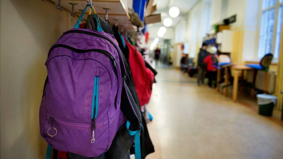 Ryggsäckar hänger på krokar i en skolkorridor i Sofia skola.