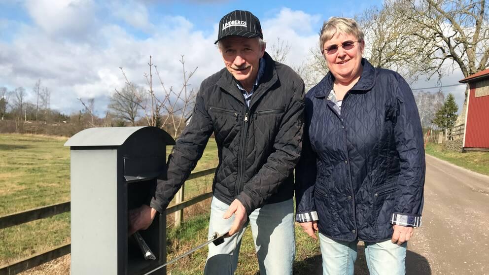 En man och en kvinna hämtar posten i landsbygdsmiljö