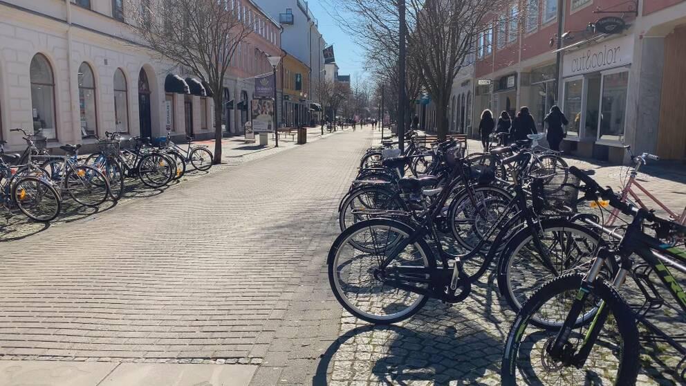En folktom gågata med cyklar, parkerade i cykelställ, i förgrunden.