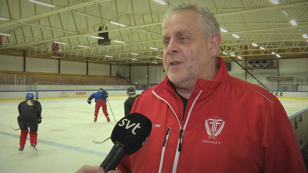 Christer Larsson i röd jacka blir intervjuad vid sidan av hockeyrinken. Tre spelare syns i bakgrunden.