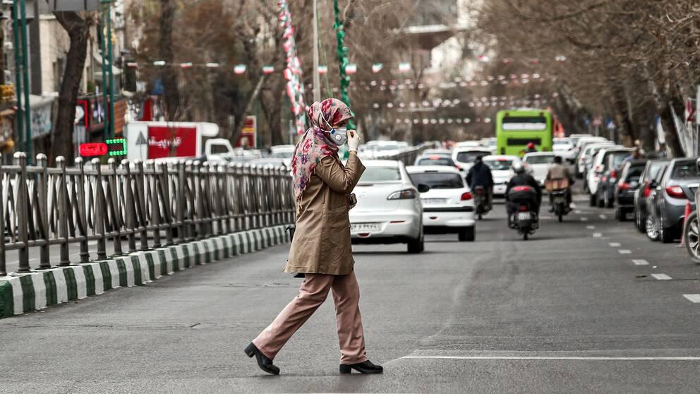 Bild på en kvinna i Iran som korsar en väg och har på sig ansiktmask och latexhandskar.