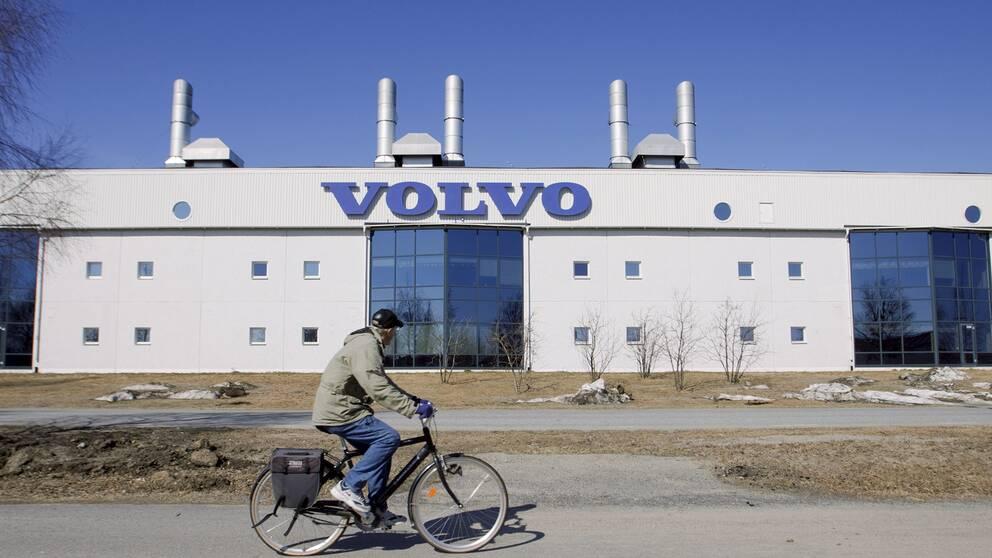 En stor fabriksfasad med en Volvoskylt på. I förgrunden cyklar en man förbi och tittar mot byggnaden.