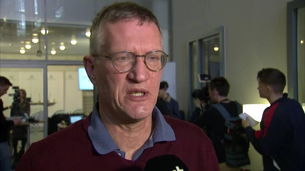 gråhårig man i glasögon intervjuas