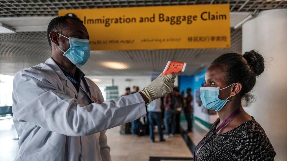 En arbetare från den etiopiska hälsomyndigheten tar tempen på en arbetare på den internationella flygplatsen i huvudstaden Addis Ababa.