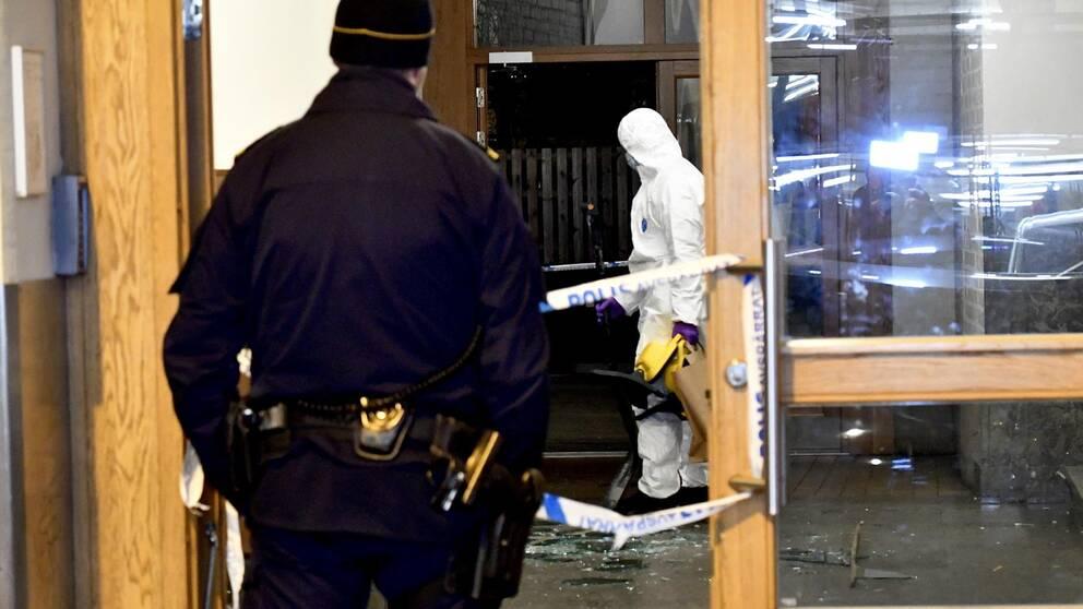 En polis och en tekniker i en entré som skadats av en explosion