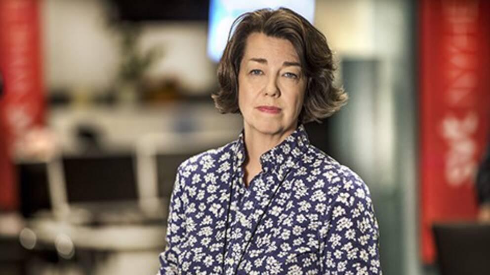 Porträttfoto på Pia Bernhardson, utrikeschef på SVT. Hon har blåvitblommig skjorta på sig.