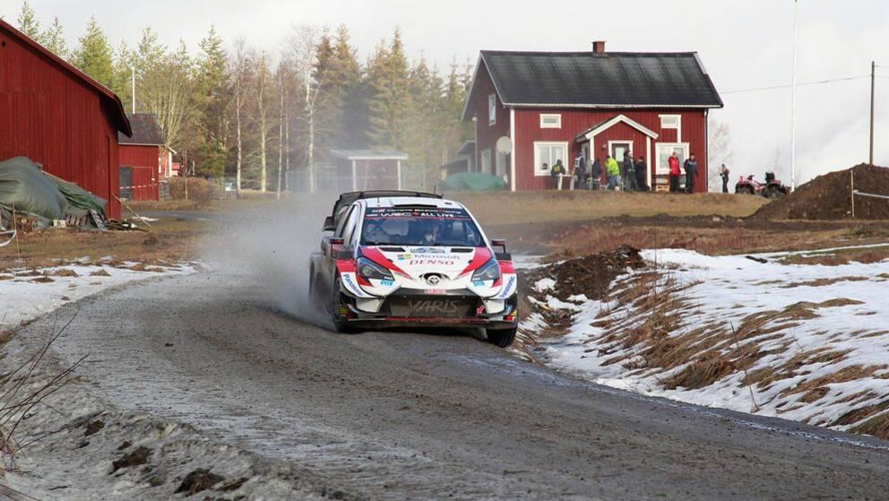 En rallybil på en grusväg med lite snö vid sidan. I bakgrunden syns lador och en röd stuga med vita knutar.