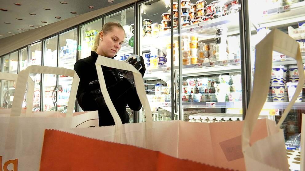I förgrunden ser man en vagn med matkassar. Julia står vid mejerihyllan bakom och plippar en creme fraiche-burk som ska packas.