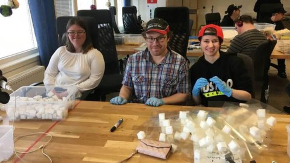 Tre personer på bilden. De sitter vid ett bord med material för att tillverka skyddsvisir framför sig.