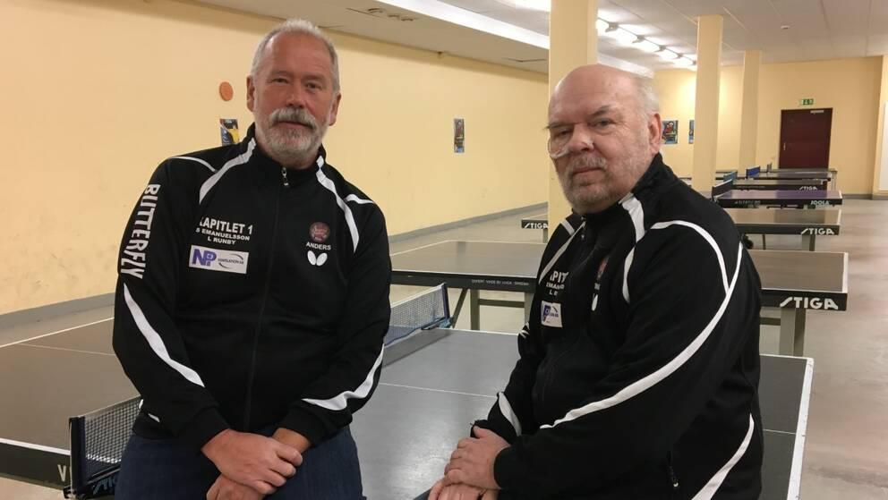 Två män sitter på ett bordtennisbord i en källarlokal.