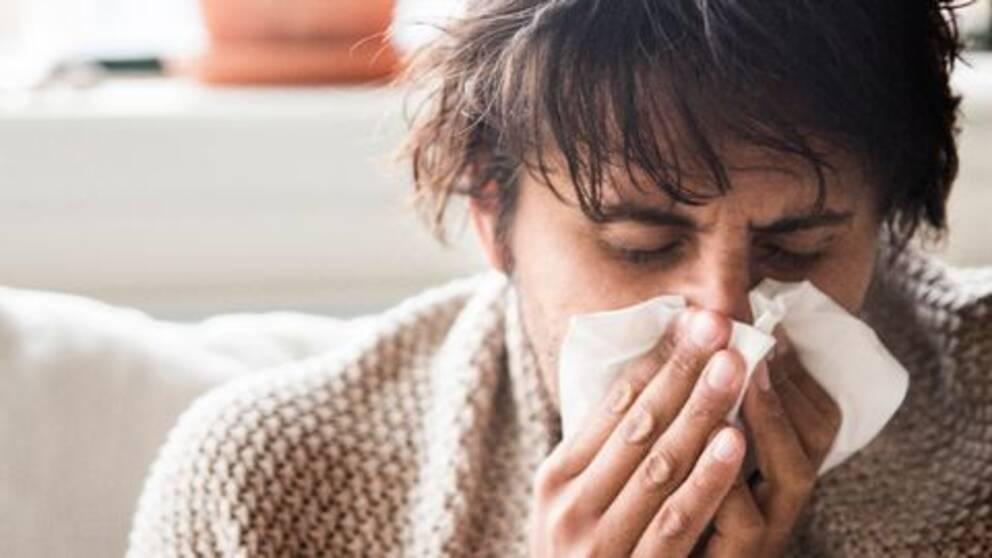 Sjuk person snyter sig i en näsduk.