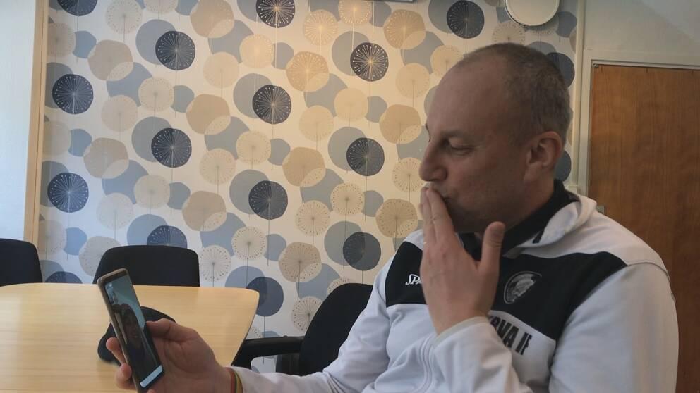 Luca Romano sitter med sin mobil i handen och facetajmar med sin familj i Italien.