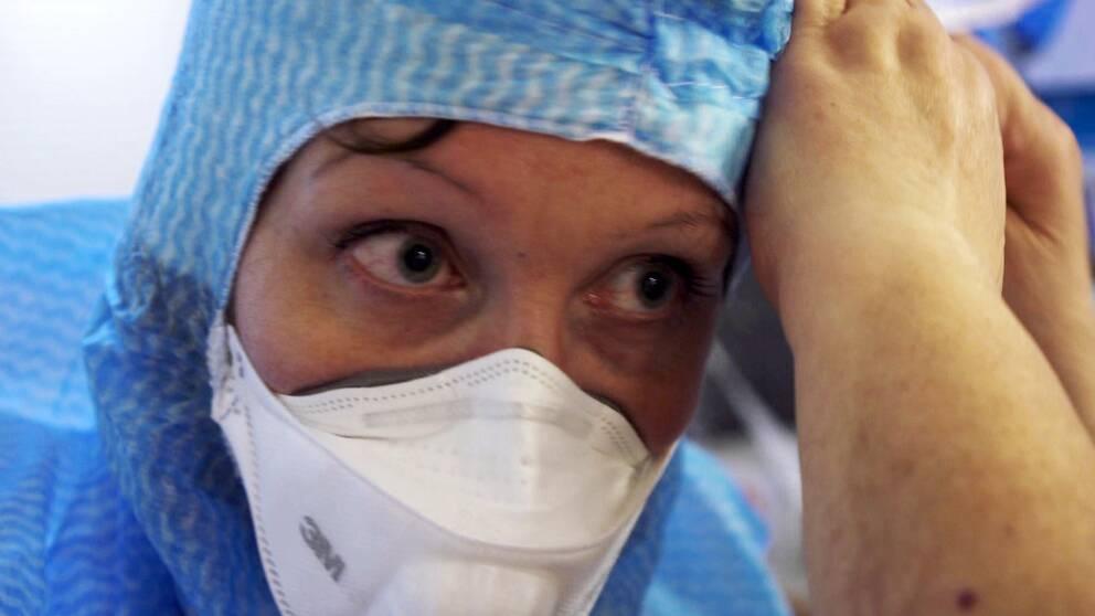 Munskydd, vårdpersonal får hjälp att ta på sig munskydd, sjukhus