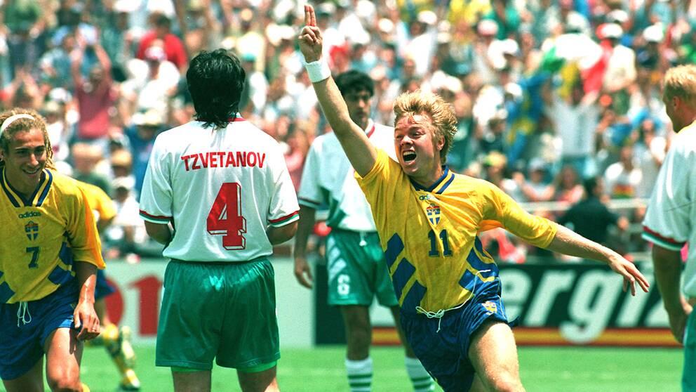 Tomas Brolin jublar under fotbolls-VM 1994 medan Henrik Larsson skyndar till för att gratulera.