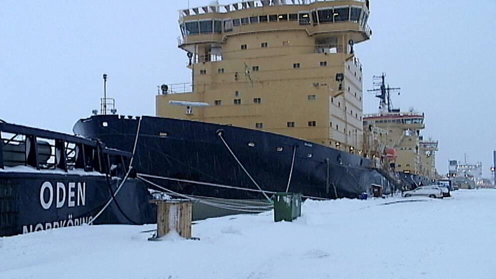 En gul och svart båt ligger vid en kaj.