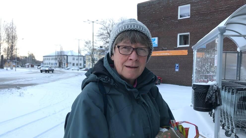 Kvinna i Nordmaling som är på väg in i butik för att handla mat. I bakgrunden syns kommunhuset och en bil som kör på en väg med nysnö och till höger i bild en rad kundvagnar. Kvinnan har grå mössa, grön jacka och en tygkasse i handen.