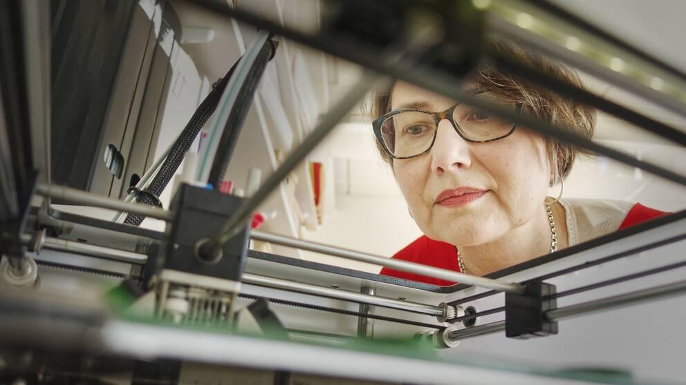 Region Gävleborgs Josephine Rydberg tittar på 3D-skrivaren som är i färd med att tillverka ett skyddsvisir.