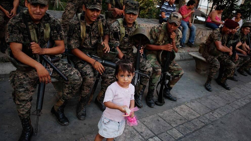 En liten flicka står bredvid honduranska militärer på rast på San Pedro Sulas centrala torg.