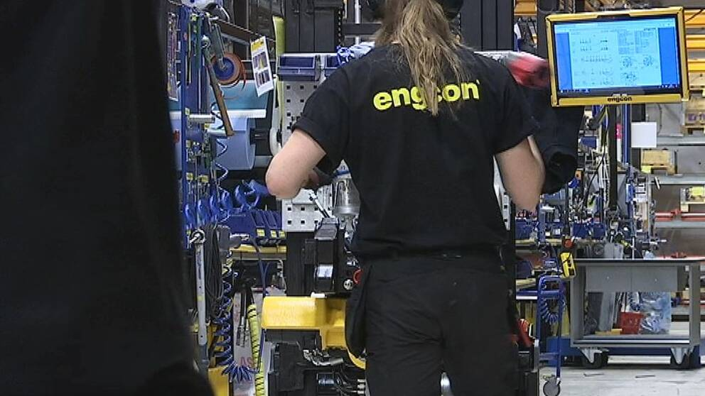 Tjej med svart t-shirt med texten Engcon i gult på ryggen, står vid en tiltrotator och monterar.