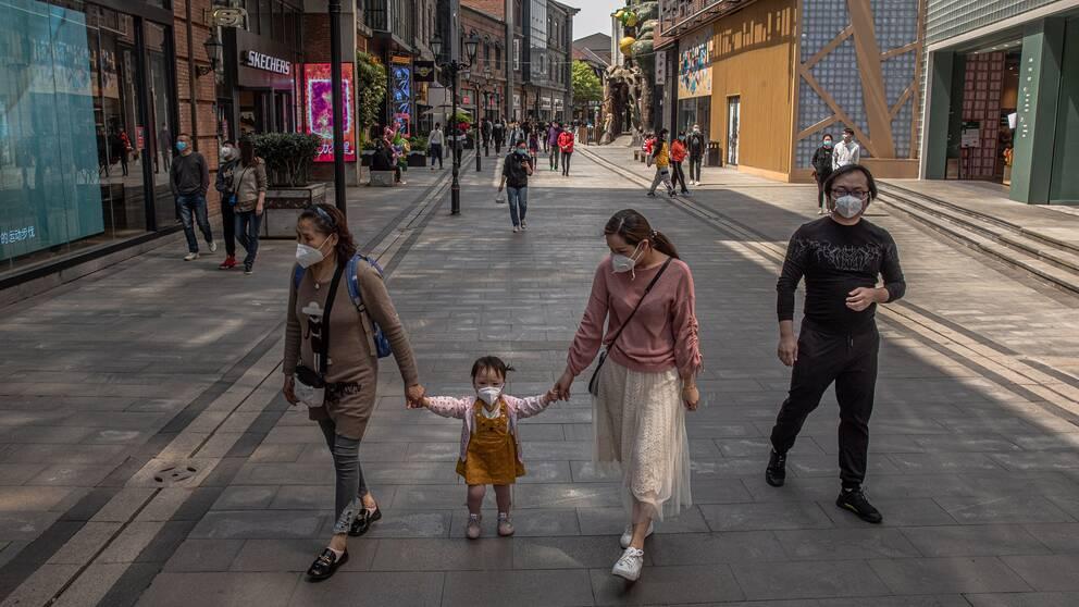 En barnfamilj som tar en promenad på en shoppinggata i Wuhan där myndigheterna nu börjar släppa på restriktionerna efter drygt två månader.