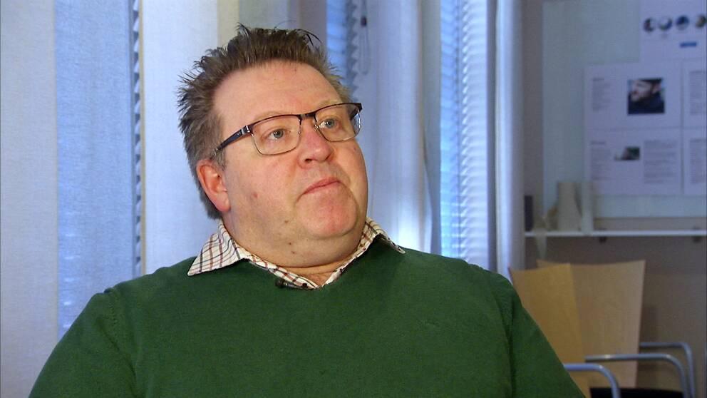 Statsvetaren Freddy Kjellström sitter i en intervjusituation inomhus.