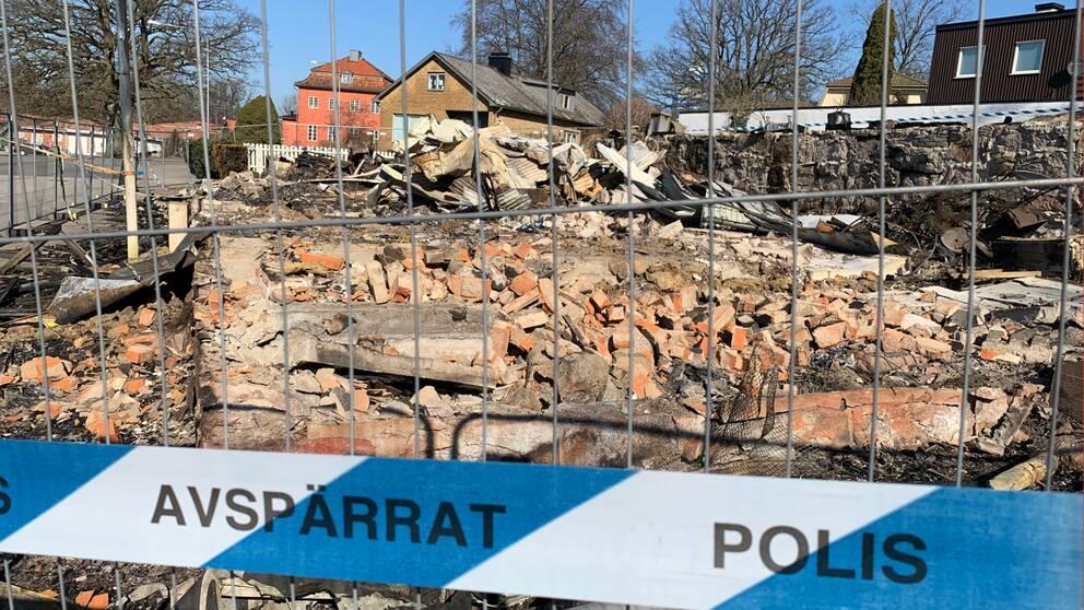 Brända ruiner bakom polisavspärrning