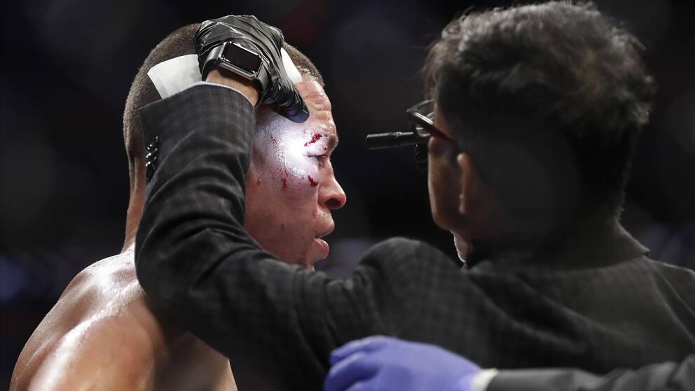 En läkare kollar närmare på UFC-stjärnan Nate Diaz under en match i november förra året.