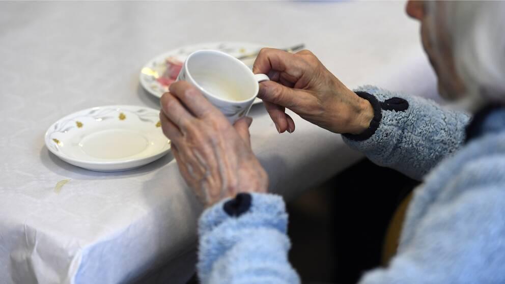 På bilden syns en äldre dam som håller i en kopp.