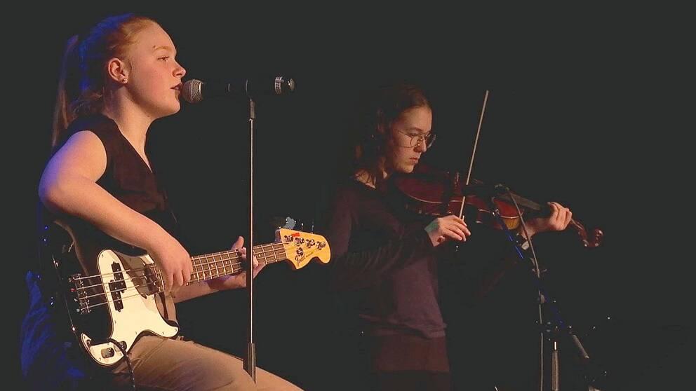 Flicka sjunger och spelar bas. Flicka i bakgrunden spelar fiol.