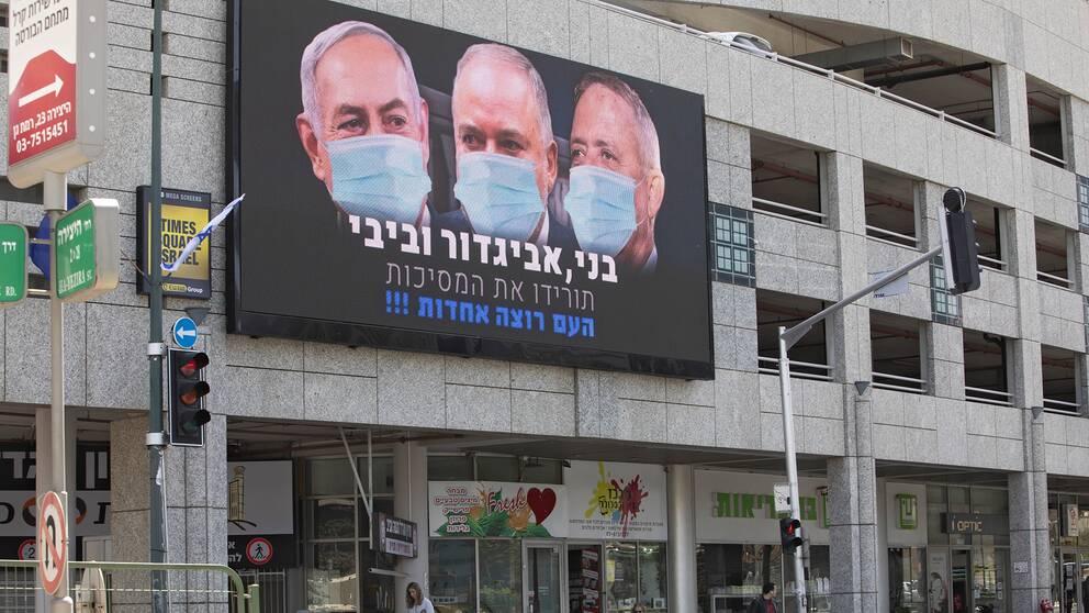 Bild på Israels premiärminister Benjamin Netanyahu, tidigare försvarsministern Yisrael Beiteinu samt oppositionsledaren Benny Gantz i förda munskydd på en reklambild i den israeliska staden Ramat Gan.