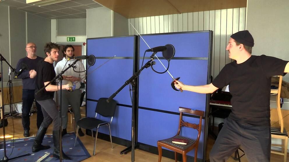 Två killar fäktas med glatt humör i en replokal. Flera mikrofoner syns uppställda och två andra män tittar intresserat på.