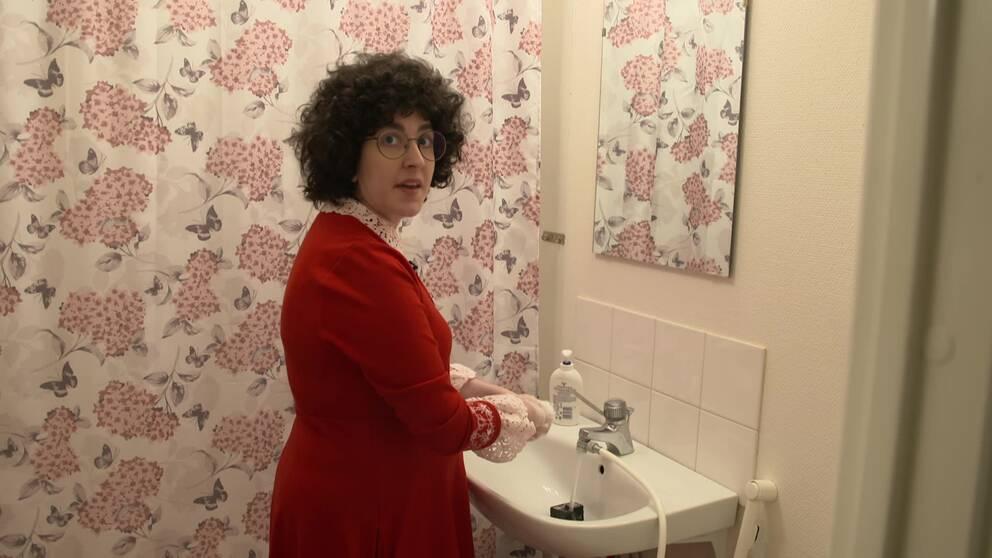 Kvinna i röd klänning tvättar händerna i badrum