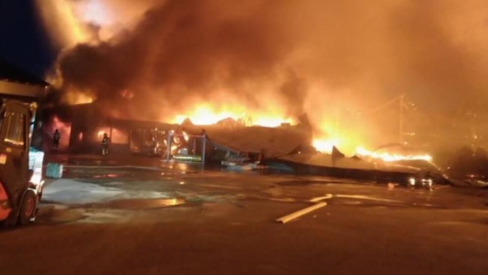 Byggnad har rasat ihop, synliga lågor syns. Personal från räddningstjänst syns i bilden.