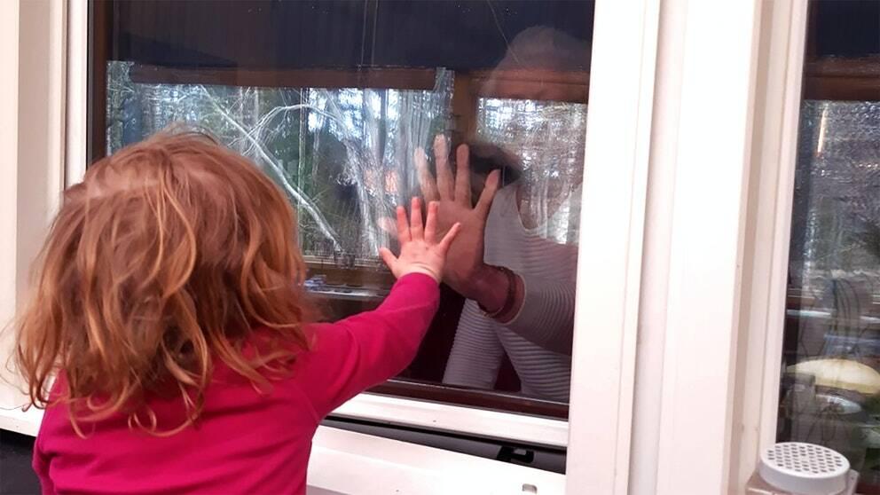 Lova hälsar på mormor genom fönsterrutan.