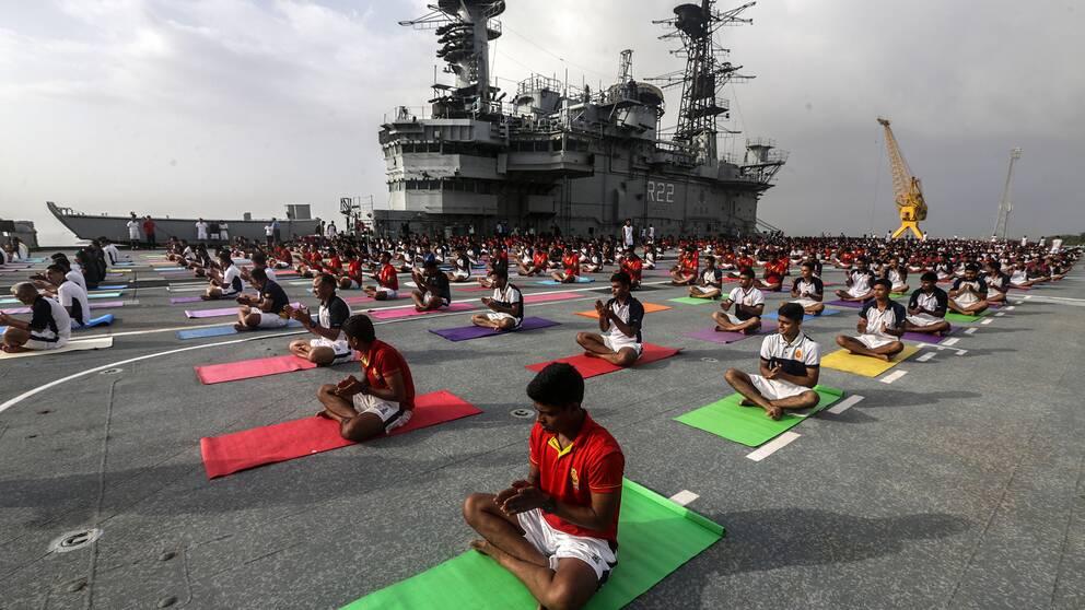 Indiska marinen utövar yoga ombord på hangarfartyget INS Viraat i Mumbai på internationella yogadagen 21 juni 2019.
