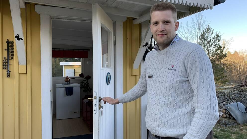Mäklare öppnar dörren till en gul sommarstuga i Rörvik i Norrtälje kommun.