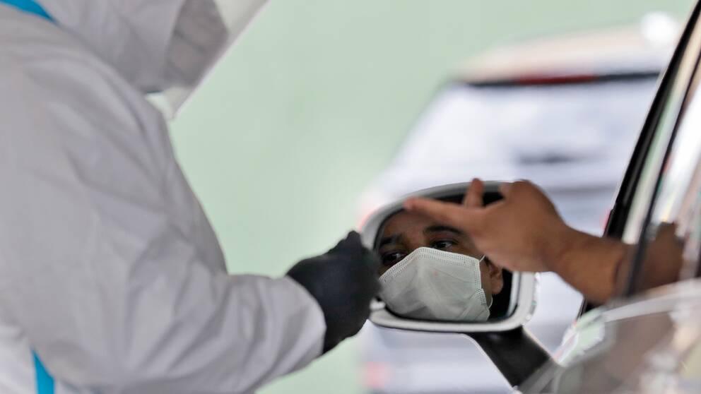 En man i New York sitter i en bil och sträcker ut fingret för att testas för antikroppar.