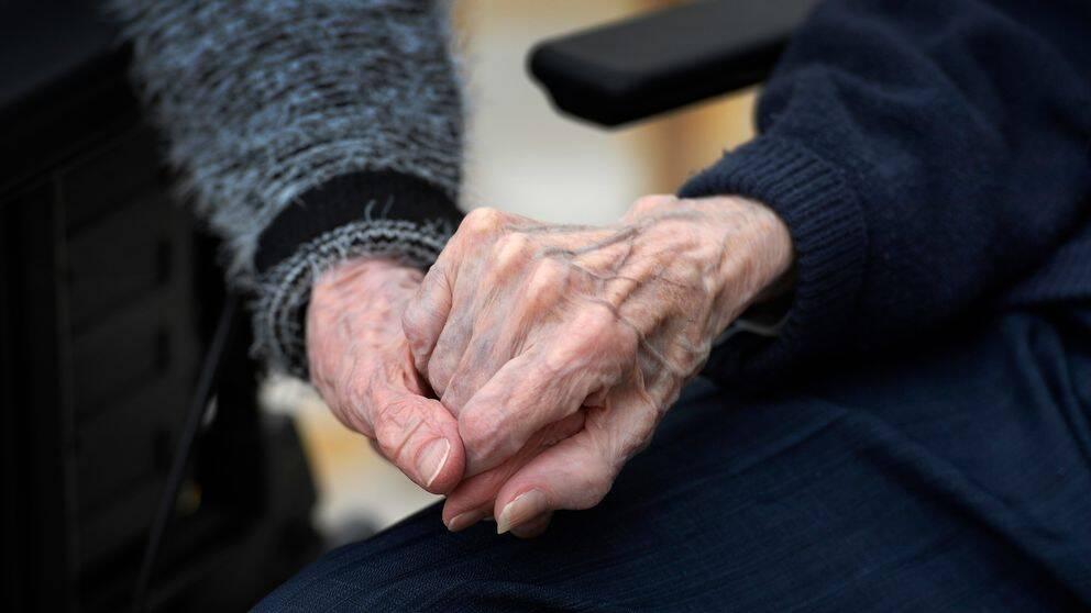 Äldre personer håller varandra i handen.