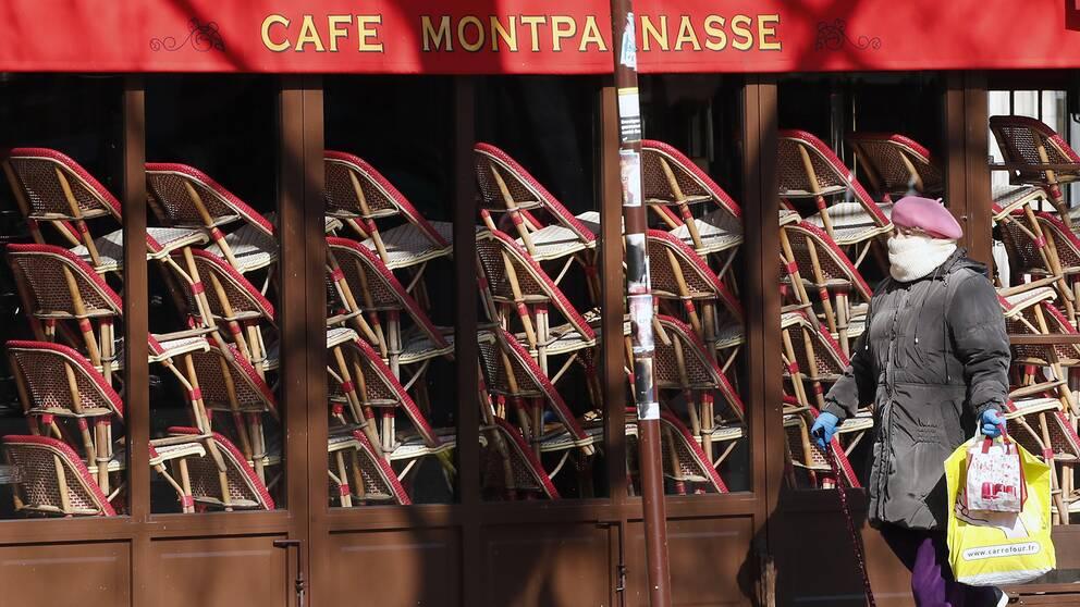 En kvinna går förbi en tillfälligt stängd restaurang i Paris.