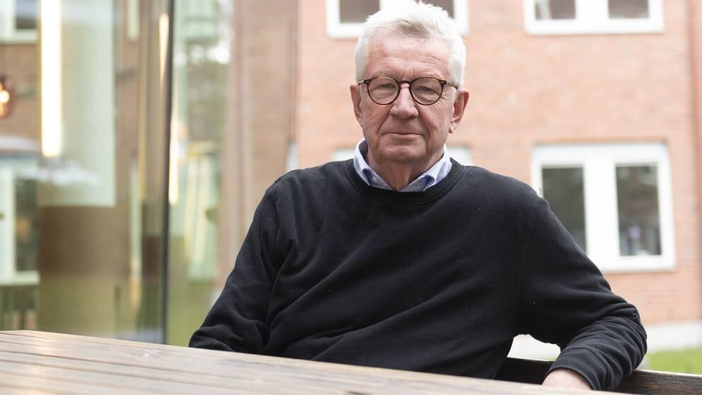 Johan Giesecke sitter på en bänk utomhus framför en byggnad.