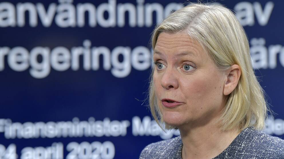 """Finansminister Magdalena Andersson syns i förgrunden, i bakgrunden (som är i fokus) syns en display där det står """"läget i ekonomin och användningen av regeringens åtgärder""""."""