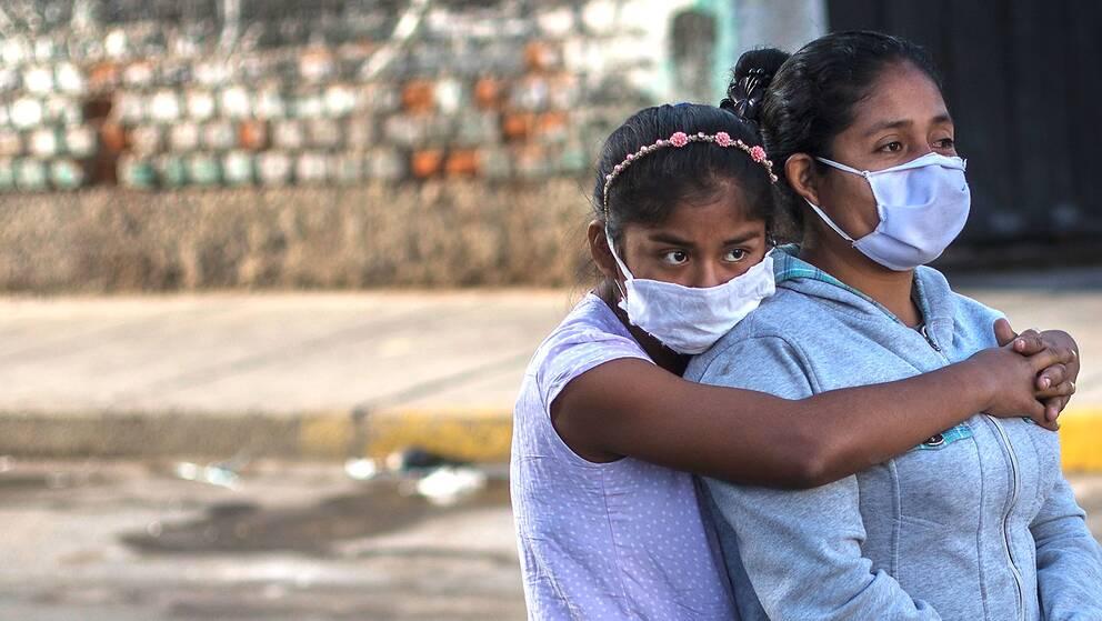 En kvinna och hennes dotter iförda ansiktsmasker