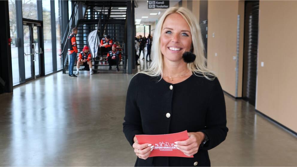 kvinna med mikrofon och manuskort i arena