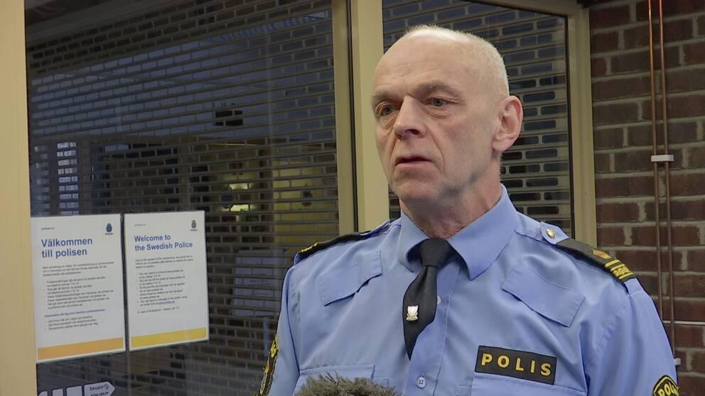 en äldre man i polisskjorta intervjuas i korridor i polishuset