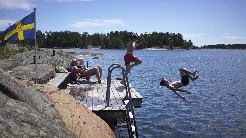 Två pojkar hoppar från en brygga. En kvinna solar sig på bryggan. Det är vackert väder, en svensk flagga vajar i vinden på en klippa intill bryggan.