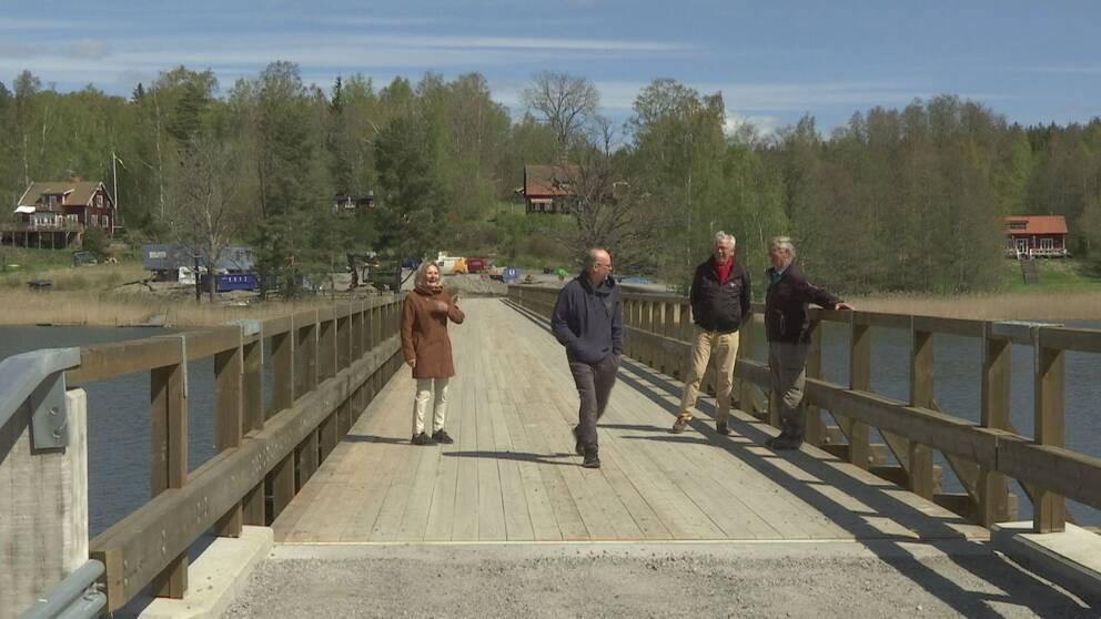 Fyra personer står på den nybyggda träbron till Hyltingeö. I bakgrunden syns pågående markarbete på andra sidan bron.